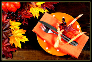 Autumn Fall background with red, brown and yellow leaves, orange pumpkin and monarch butterfly on dark recycled rustic wood table with orange table place setting.